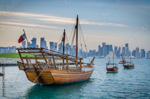 Dhows moored off Museum Park in central Doha, Qatar, Arabia, with some of the buildings from the city's commercial port in the background Wallpaper Mural