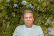 man sitting in front of Plumbago capensis
