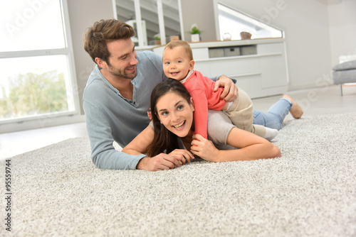 Photo Parents and baby girl laying on carpet,