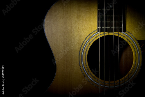 Valokuva  Acoustic guitar isolated on black background, horizontal view, low key image