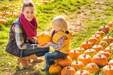 Smiling Woman And Child Choosing A Pumpkin On Farm