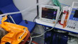 Paramedic monitoring obese senior patient condition in ambulance during transportation
