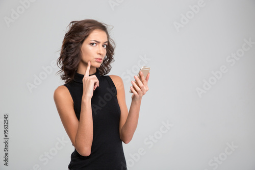 Fotografie, Obraz  Annoyed young woman using cellphone