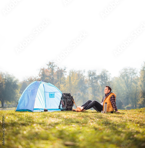 Canvas Prints Camping Relaxed hiker sitting next to a blue tent