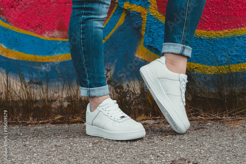 Fotografía  White sneakers on girl legs on the graffiti background