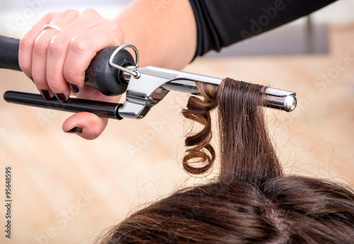mata magnetyczna Hairstylist using a curling iron or tongs