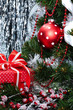 Новогодний подарок в красной коробке и красный шар на елке