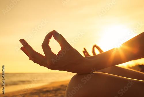 Fotografía  Primer plano de mano de una mujer meditando en la playa.