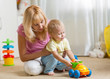 Mother and child son play with toy car on nursery floor