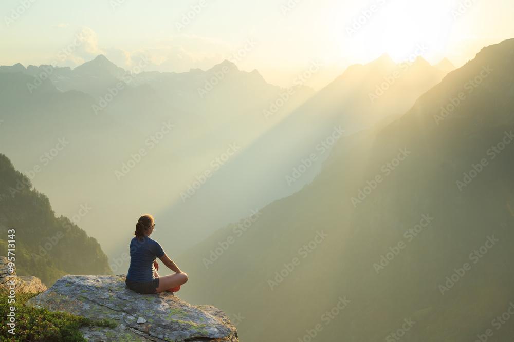 Fototapeta Woman relaxing en enjoying the summer sunset in the mountains.