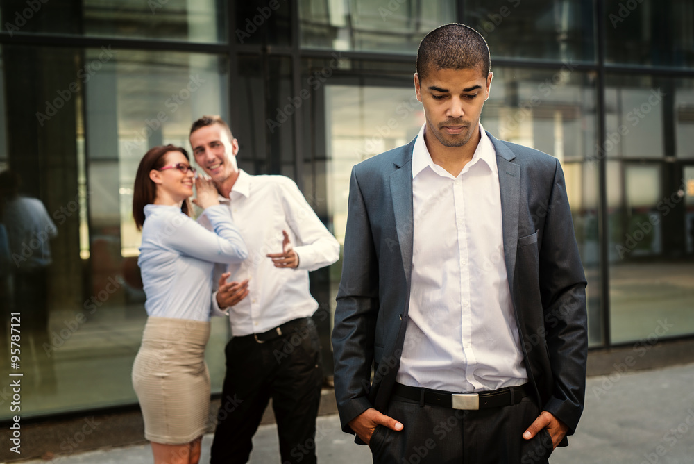 Fototapety, obrazy: Gossip colleagues in front of their office, handsome businessman portrait in front and gossip out of focus in background.