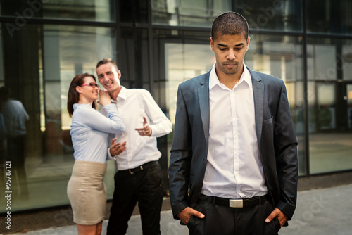 Fototapeta Gossip colleagues in front of their office, handsome businessman portrait in front and gossip out of focus in background. obraz
