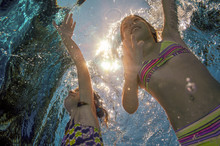 Children Swim In Pool Or Sea Underwater, Happy Active Girls Have Fun In Water, Kids Sport On Family Vacation