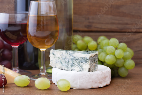 Wine pouring into wine glass. Cheese, grapes in restaurant. Poster