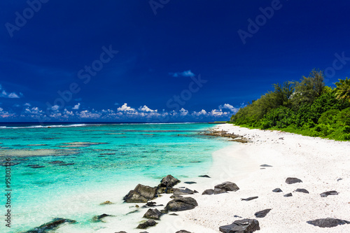 Fotografie, Obraz  Beach with white sand and black rocks on Rarotonga, Cook Islands