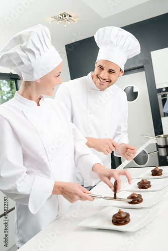 student and teacher in a professional cook school kitchen preparing