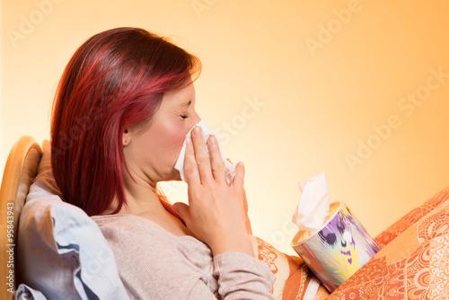 Fotografia  Ragazza raffreddata si soffia il naso a letto