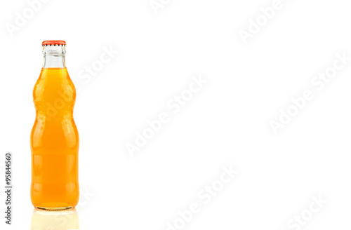 Fotografia  Glass bottle of orange soda isolated on white background