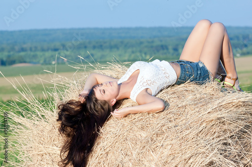 Valokuva  young beautiful long haired girl posing in shorts lying on a haystack