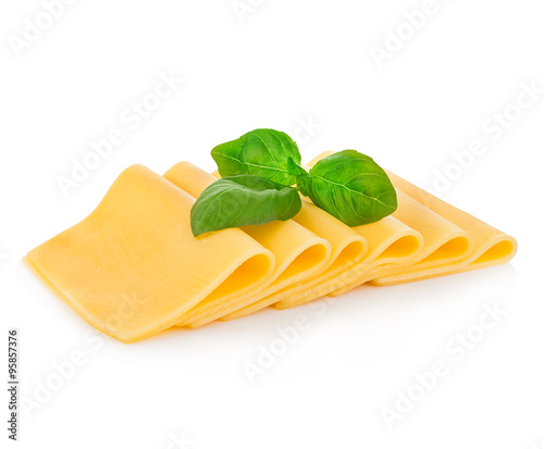 Slices of cheese with fresh basil leaves close-up isolated on a white background.