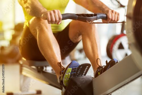 Poster Fitness man training on row machine in gym