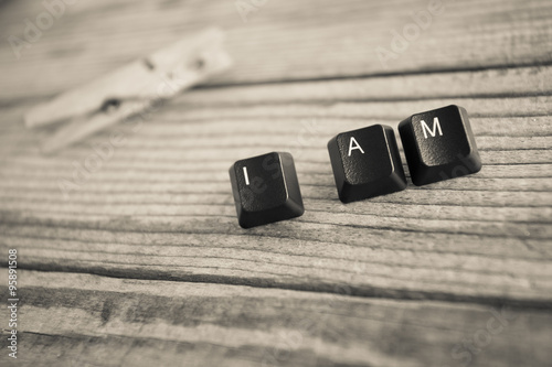 Fotografia, Obraz  I AM wrote with keyboard keys on wooden background, black and wh