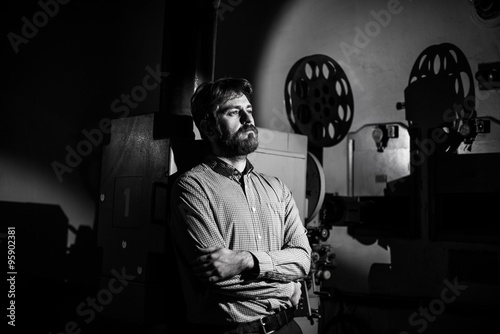 Photo  man standing near a film projector in the room projectionist