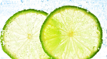 Fototapeta Owoce lime with bubbles isolated on white