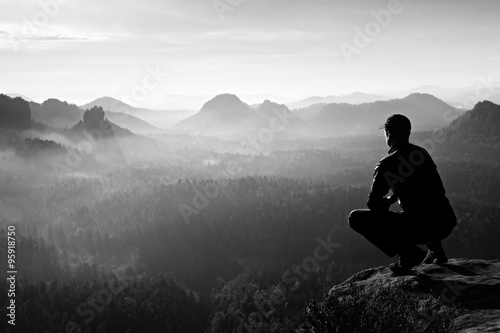Runner in red cap and in dark sportswear in squatting position enjoy mountain scenery