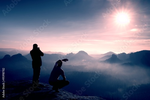 Poster Rose clair / pale Two friends. Hiker thinking and photo enthusiast takes photos stay on cliff. Dreamy fogy landscape, blue misty sunrise in a beautiful valley below