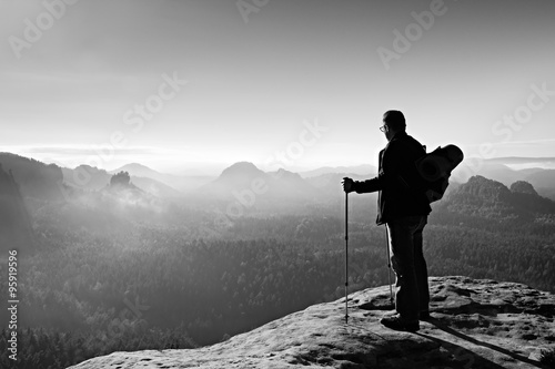 Backpacker with eyeglasses and poles in hand  Sunny day in rocky