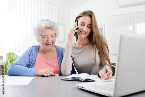 Fotografie, Obraz  young woman helping an old senior woman doing paperwork and administrative proce