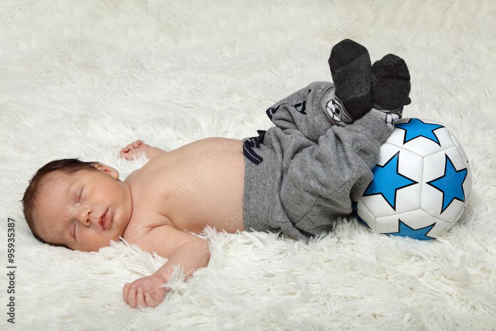 Fototapeta Śpiące niemowlę z piłką, noworodek.