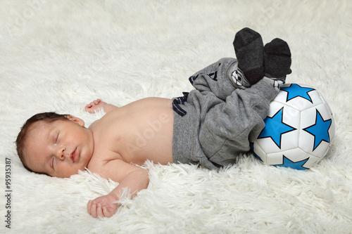 Fototapeta Śpiące niemowlę z piłką, noworodek. obraz