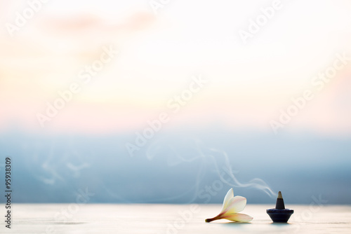 Fototapeta Smoke incense cones with plumeria flower on sunset obraz