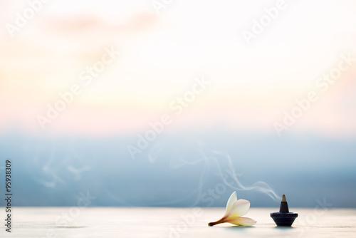 Fotografía  Conos de incienso de humo con Plumeria flor en la puesta del sol