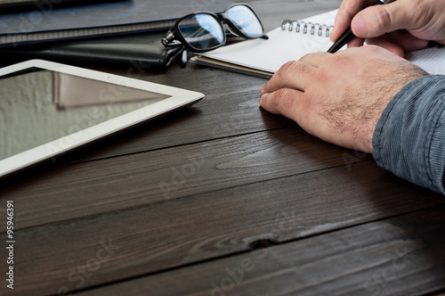 male hands writing in a notebook on the office table Canvas Print