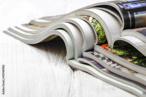 Fotografie, Obraz  stack of magazines on a white wooden background