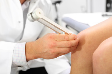 Kamerton, badanie ortopedyczne.Lekarz ortopeda bada kolano pacjenta przy użyciu kamertonu.