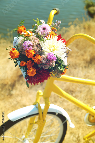 Beautiful yellow bicycle with bouquet of flowers in basket, outdoors - 95969986
