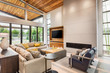 Beautiful living room interior with vaulted ceilings, hardwood floors, sliding glass doors, and fireplace in new, modern luxury home