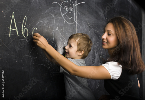 little cute boy with young teacher in classroom studying