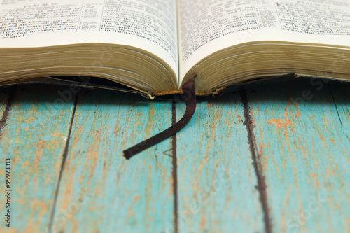 Fotografie, Obraz  Opened Bible with a bookmark on Wood