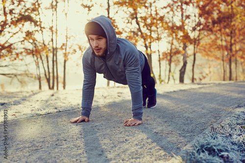 Poster Glisse hiver Young runner doing push ups exercise during cold autumn morning