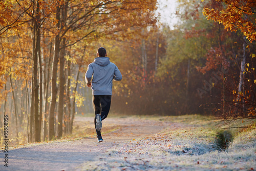 Fotografie, Obraz  Young man running at park during autumn morning.