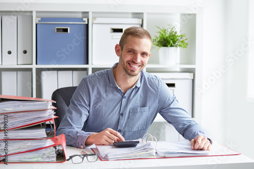Pinturas sobre lienzo  Smiling businessman calculates taxes