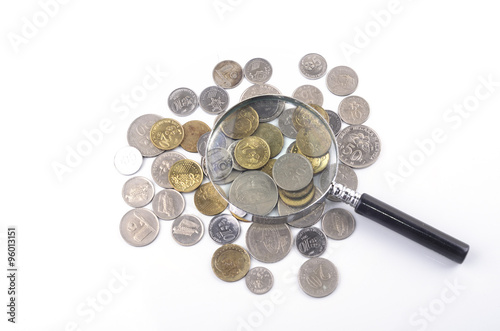 Magnifier glass and coin on white background. Financial concept Canvas Print