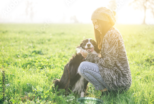 Photographie Young woman playing and enjoying the time with her dog