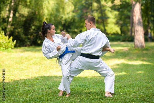 Staande foto Vechtsport Young woman and man practicing martial arts outdoors