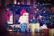 little boy with presents looking at fireplace on christmas